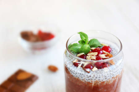 Chocolate chia seed pudding with cranberry and crushed almonds on wooden table