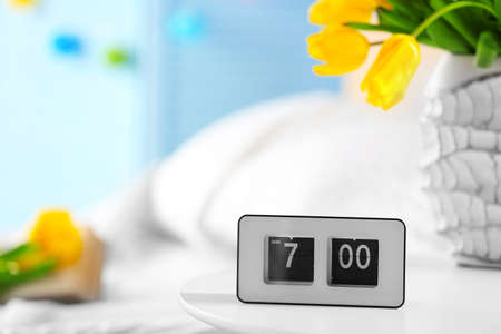 Number alarm clock on bedside table in a room