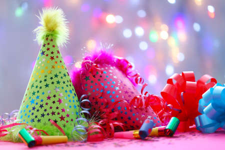 Party hats and other stuff on blurred garland background 스톡 콘텐츠