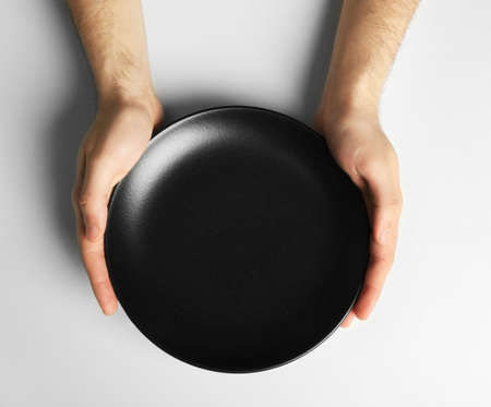 Male hands holding black plate, isolated on white