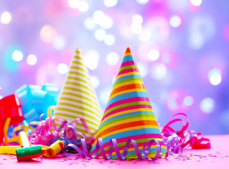 Party hats and other stuff on blurred garland background Stock Photo
