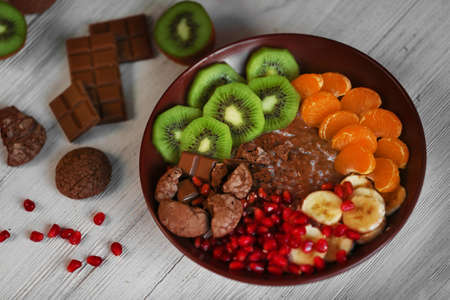 Bowl with chocolate cookies, sliced fruits, chia and pomegranate seeds on wooden table
