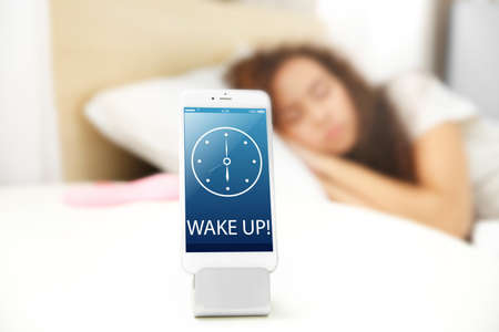 Mobile alarm clock and sleeping girl in bedroom Stock Photo