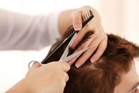 Professional hairdresser making stylish haircut, closeup Stock Photo