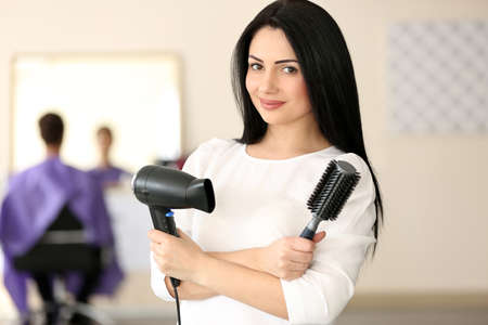 Professional hairdresser with comb and hairdryer