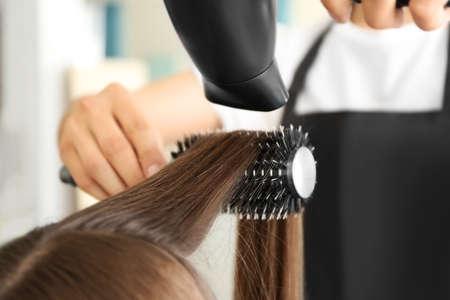 Professional hairdresser drying hair
