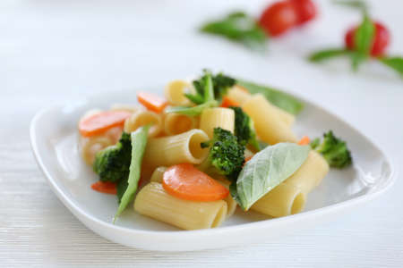 Boiled rigatoni pasta with carrot, broccoli and basil on white plate