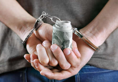 Man in handcuffs holding dollar banknotes behind the back, close up Stock Photo