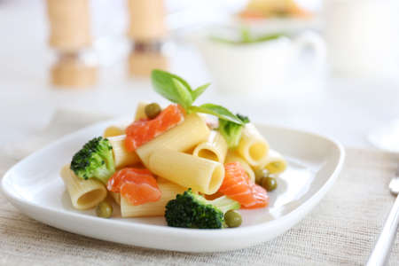Boiled rigatoni pasta with salmon and broccoli on white plate