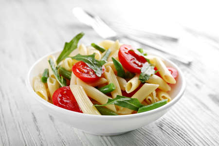 Boiled penne pasta with tomatoes, French bean and arugula on white plate 免版税图像