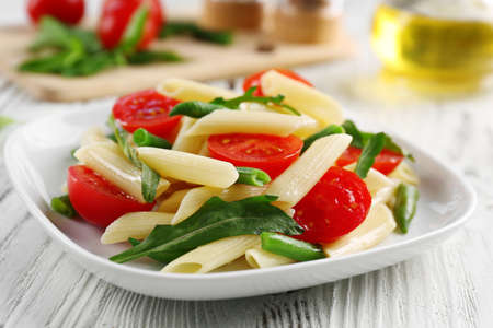 Boiled penne pasta with tomatoes, French bean and arugula on white plate Stock Photo