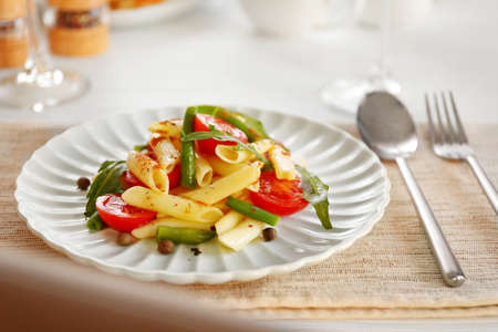 Boiled penne pasta with tomatoes, French bean and arugula on white plate Archivio Fotografico