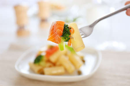 Fork with impaled boiled rigatoni pasta with salmon and broccoli, close up