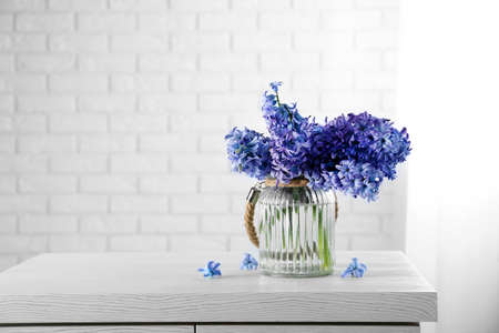 Beautiful hyacinth flowers in glass vase against brick wall background