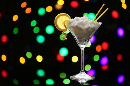 Martini glass with lump sugar on dark bokeh background