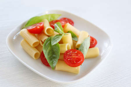 Boiled rigatoni pasta with fresh tomatoes and basil on white plate