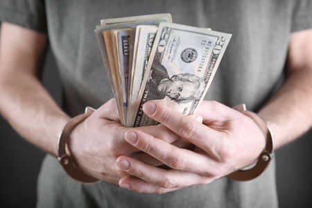 Man in handcuffs counting dollar banknotes, close up Stock Photo