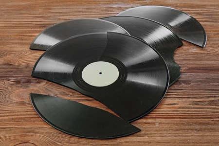Broken old vinyl records on wooden background