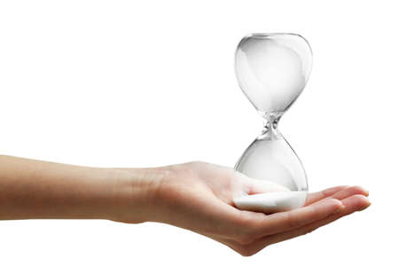 Hourglass in female hand on grey background Stock Photo