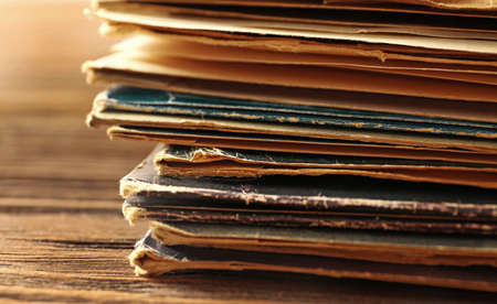 Stack of old vinyl records on wooden background