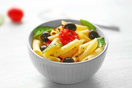 Cooked penne pasta with olives, fresh tomatoes and basil in blue bowl on wooden table
