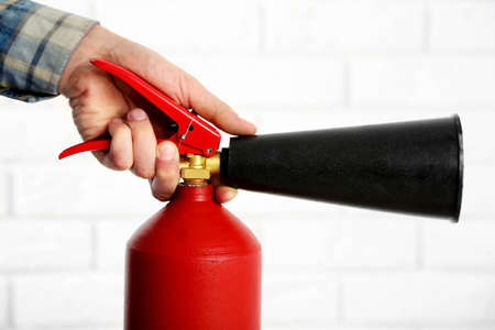 Man holding the fire extinguisher on white brick wall background