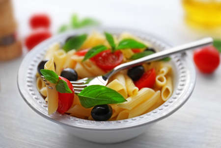 Cooked pasta and fresh tomato impaled on a fork, close up Stock Photo