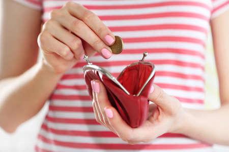 Młoda kobieta dostaje monety euro z kiesy