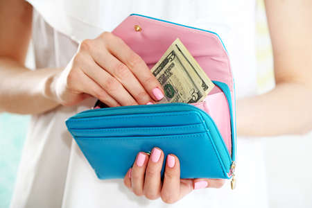 Young woman getting dollars banknotes from purse