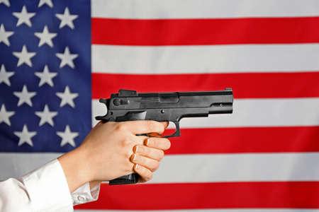Woman holding handgun on USA national flag background Stock Photo