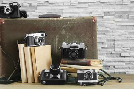 Vintage cameras with old books on brick wall background