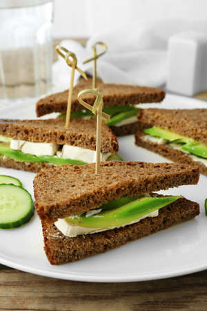 Vegetarian avocado sandwich with dark rye bread on a white plate Imagens