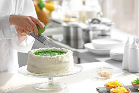 Female hands decorating cake  with lime zest 스톡 콘텐츠