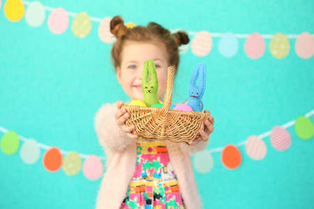 Little girl holding wicker basket with colorful Easter eggs on decorated blue wall background