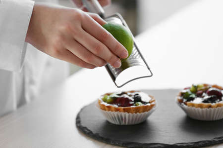 Female hands decorating fruit tarts with lime zest Stock Photo