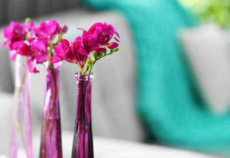 Vases with flowers on the table in the room Stock Photo