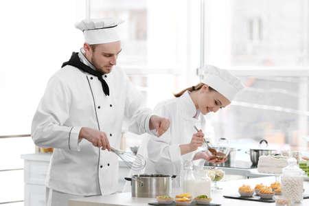 Mannelijke en vrouwelijke chef-koks die bij keuken werken Stockfoto
