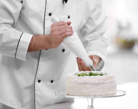Male hands decorating cake with cream. Foto de archivo