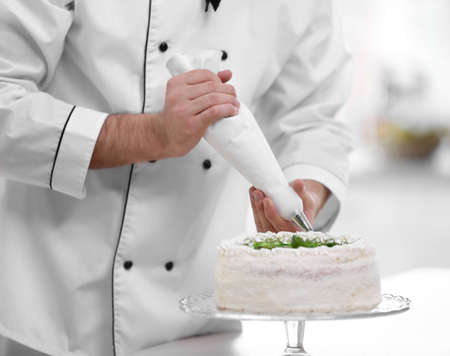 Male hands decorating cake with cream. Archivio Fotografico