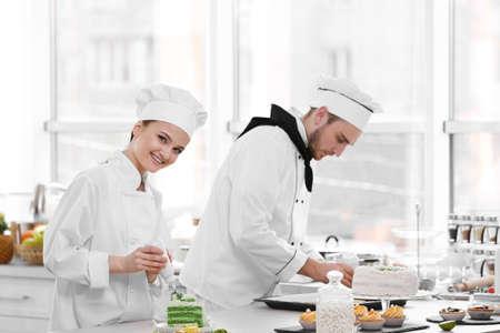 Mannelijke en vrouwelijke chef-koks die bij keuken werken