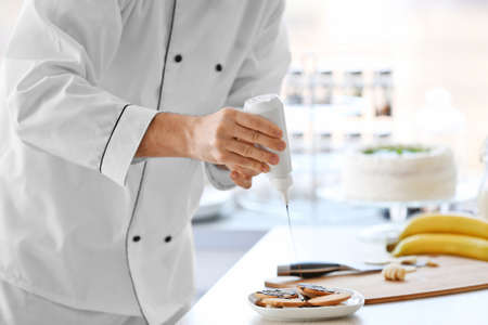 Male chef decorating cookies with chocolate. Stock Photo