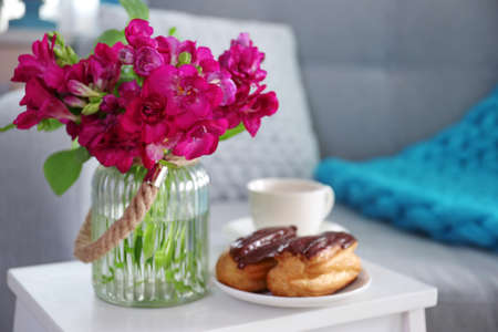 Flowers and pastry on white table in living room