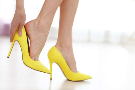 Woman taking off yellow high heels shoes. Фото со стока