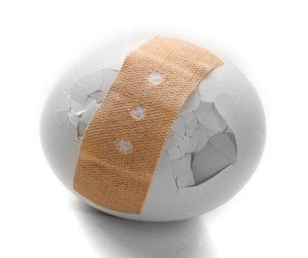 Cracked egg wrapped in court plaster isolated on white