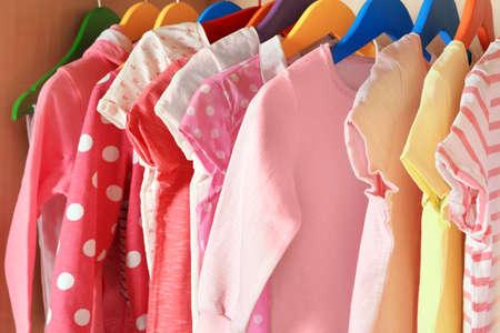 De kleren van het meisje op hangers in de garderobe, close-up