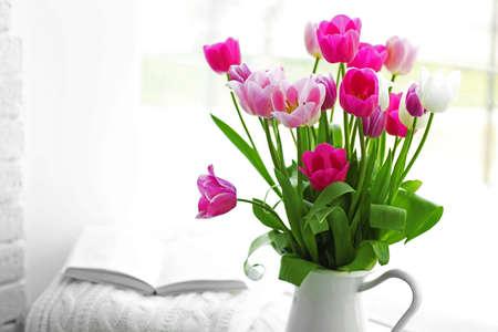 Beautiful fresh tulips on windowsill background