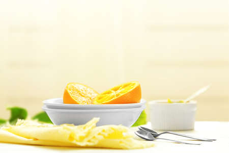 Eating oranges with spoon on white table Stock Photo