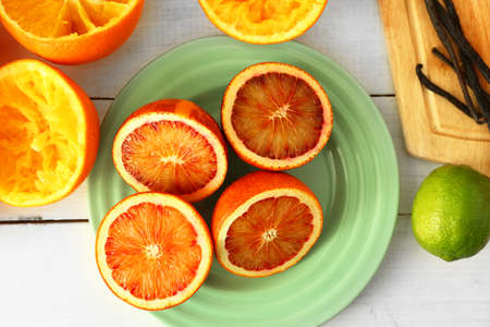 Halved Sicilian oranges on a plate on white wooden table