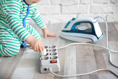 Little child playing with iron and electric power bar at home Reklamní fotografie