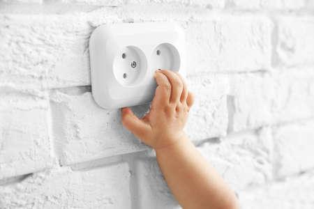 Weinig baby die met contactdoos op de muur speelt